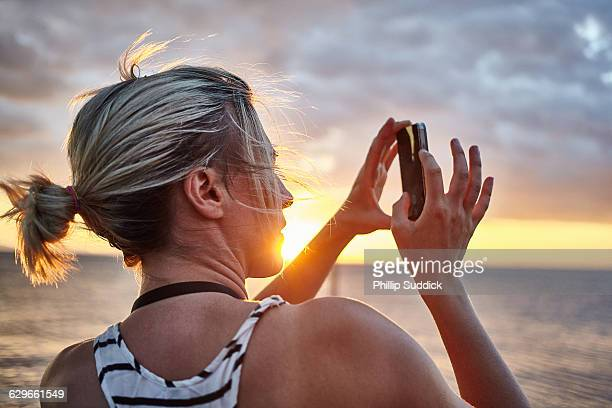 Female photographer taking pictures on peer sunset