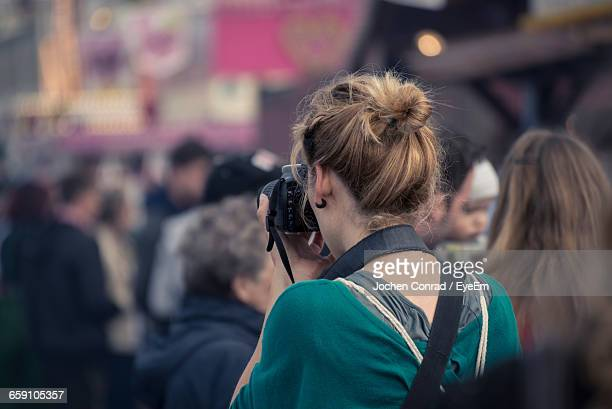 Female Photographer Taking Shot Of Street