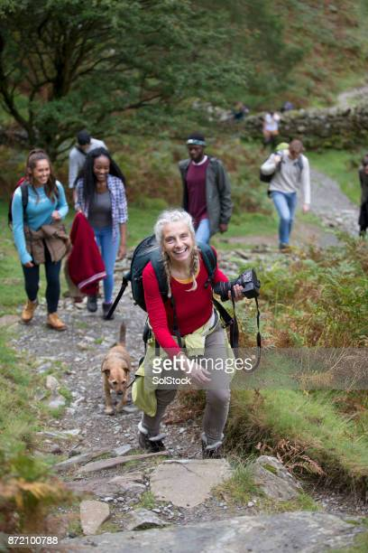 female photographer walking up a mountain. - cumbria stock photos and pictures