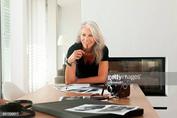 female photographer with photographs and old fashioned large format camera on a table - older woman bending over stock pictures, royalty-free photos & images