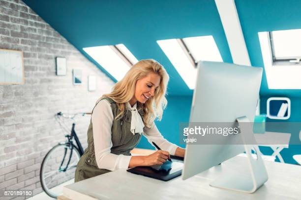 female photographer working in her office - retouched image stock photos and pictures