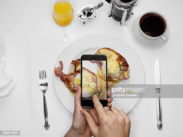 female photographing her food with mobile phone - mimosa stockfoto's en -beelden