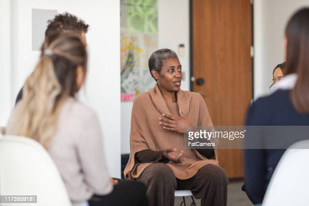 female phycologist leads group therapy session - victim stock pictures, royalty-free photos & images