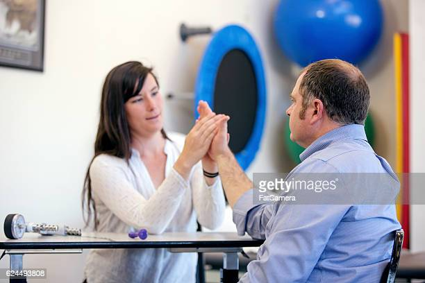 Female physical therapist adjusting adult male wrist during rehab