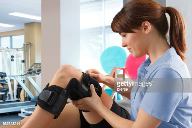 female physical therapist adjusting knee brace on female patient - brace stock pictures, royalty-free photos & images