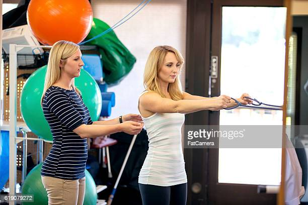 Female physical therapist guiding female patient with a therapy exercise
