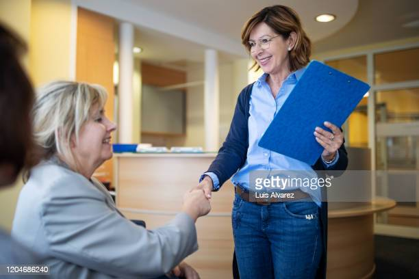 female physical therapist handshaking with a disabled woman - differing abilities fotografías e imágenes de stock