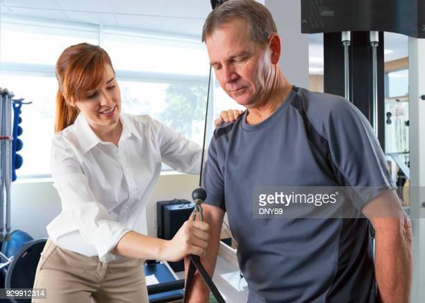 Weibliche Physiotherapeut anweist männlichen Patient auf ordnungsgemäße Verwendung von Trainingsgeräten