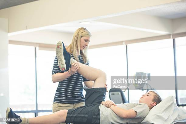 Female physical therapist working with a teenage patient