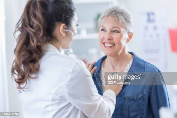 female physician listens to senior patient's heart - doctor's surgery stock pictures, royalty-free photos & images