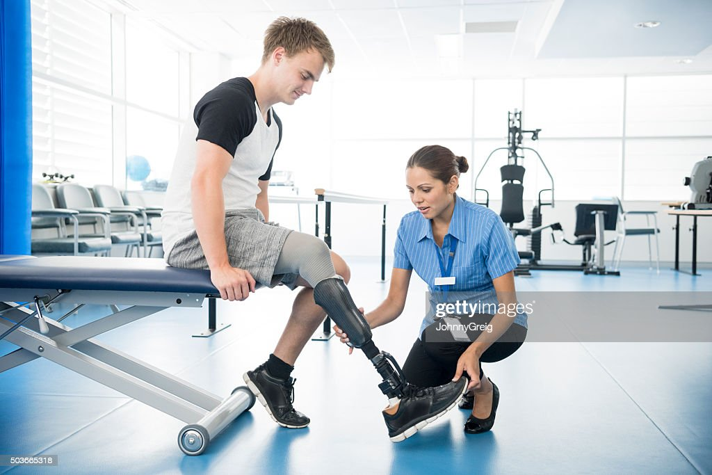 Female physiotherapist helping young man with prosthetic leg : Stock Photo
