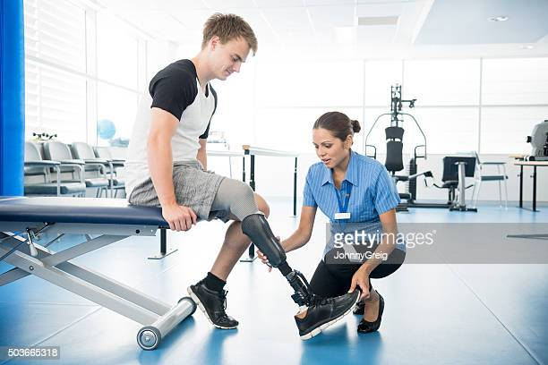 Female physiotherapist helping young man with prosthetic leg