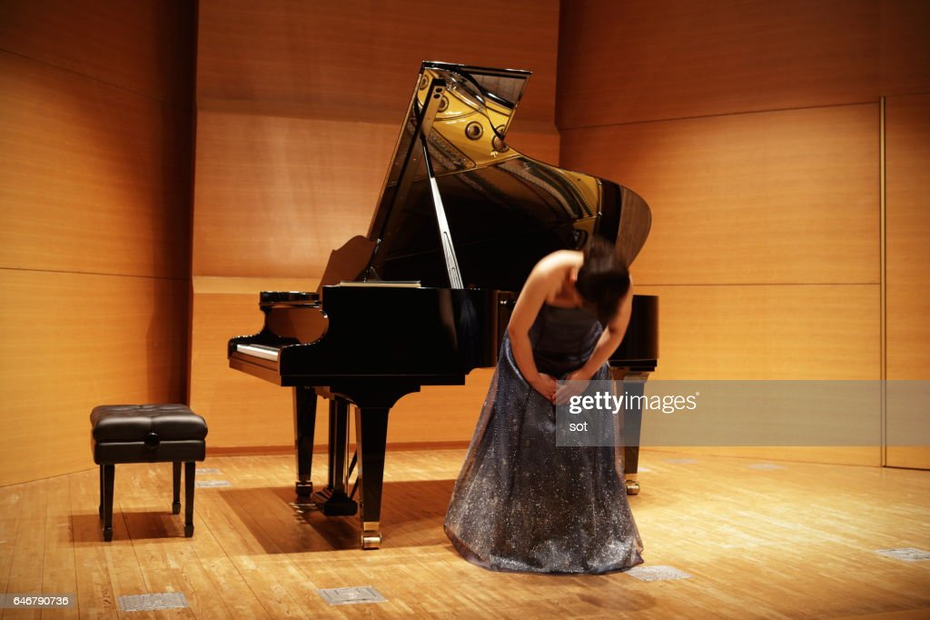 Female pianist bowing on concert hall stage : ストックフォト