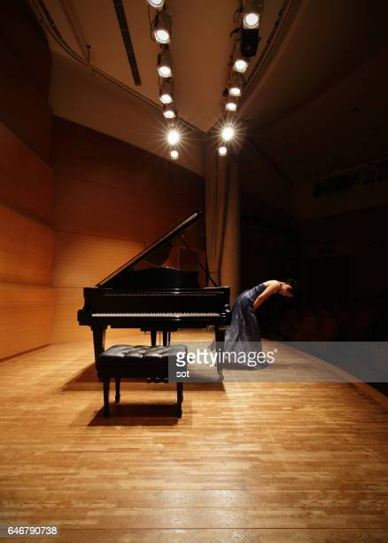 Female pianist bowing on concert hall stage