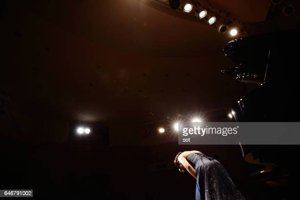 Female pianist bowing on concert hall stage with grand piano,rear view