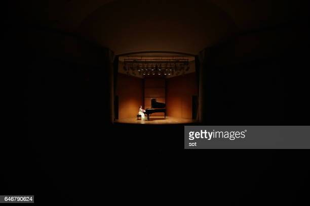 Female pianist playing grand piano at concert hall