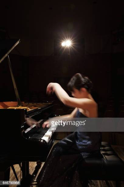 Female pianist playing grand piano at concert hall stage