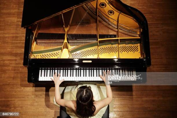 Female pianist playing grand piano at concert hall stage,aerial view