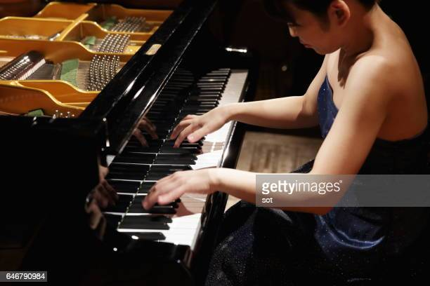 Female pianist playing grand piano,close up
