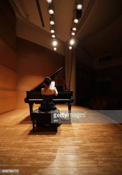 Female pianist preparing to play the grand piano on stage of concert hall stage,rear view
