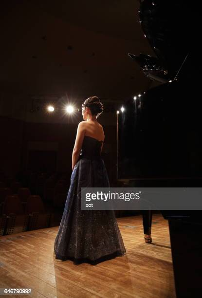 Female pianist standing on concert hall stage with grand piano,rear view