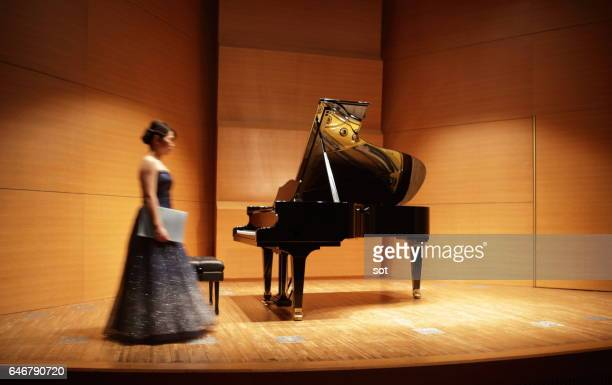 Female pianist walking on concert hall stage with music sheet