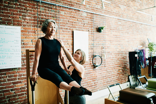 Female pilates instructor assisting mature student on high-low chair during class in exercise studio - gettyimageskorea