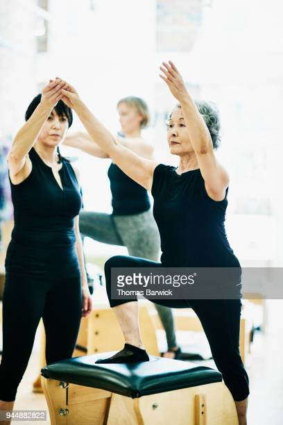 Female pilates instructor helping mature student on pilates chair during class in fitness studio