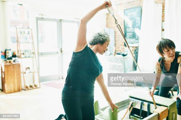 Female pilates instructor helping mature woman do side bend press on reformer during pilates class