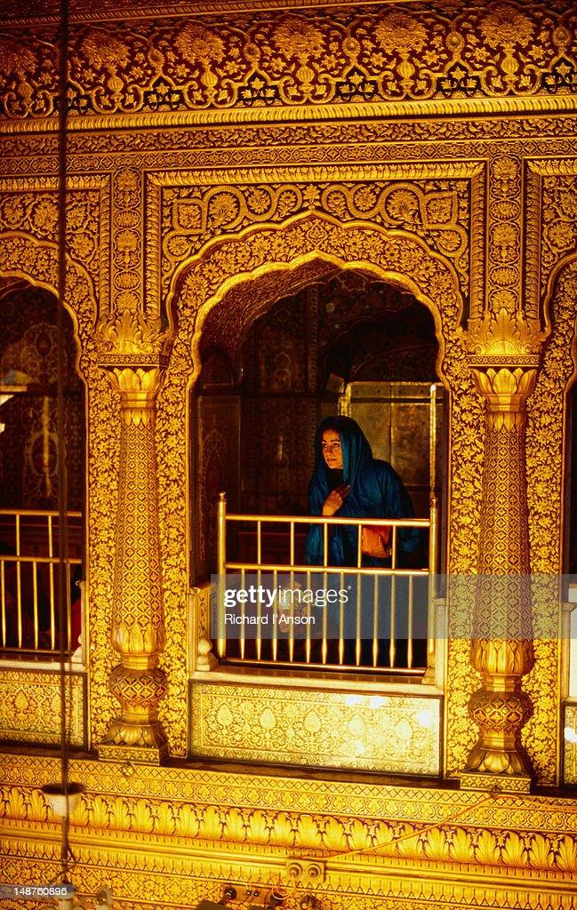 A female pilgrim stands inside the aptly named Golden Temple (Harmandir Sahib) in Amritsar.