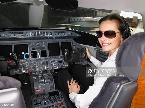 Female pilot in cockpit of private jet.