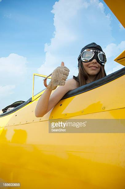 female pilot in vintage yellow airplane