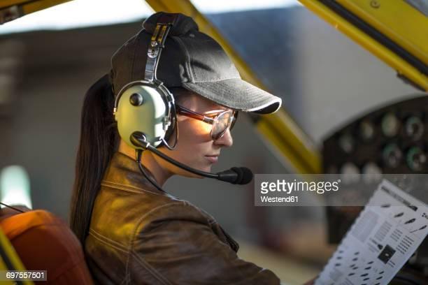 Female pilot inspecting light aircraft cockpit