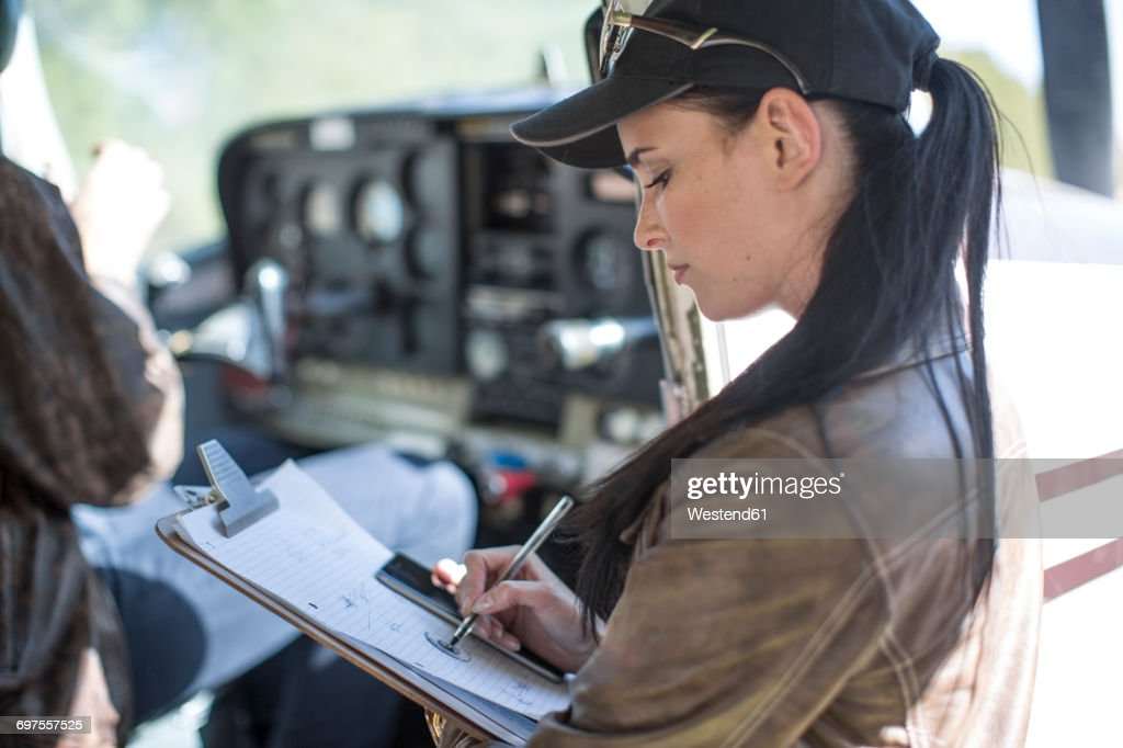 Female pilot inspecting light aircraft cockpit : Stock Photo