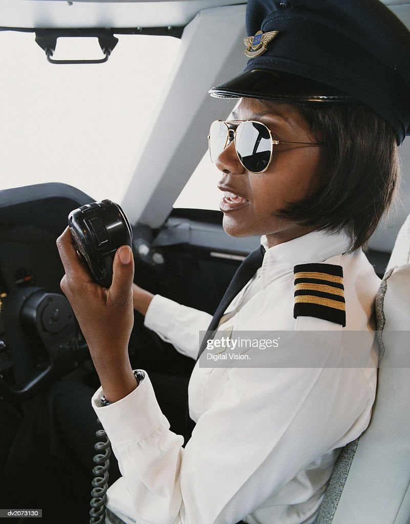 Female Pilot Talking into a Radio : Stock Photo