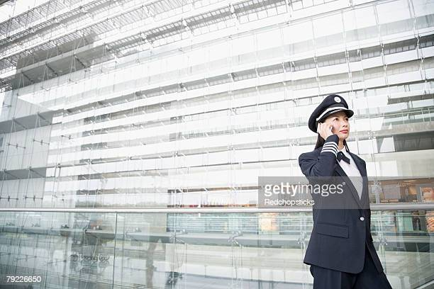female pilot talking on a mobile phone - uniform cap stock pictures, royalty-free photos & images