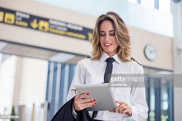 Female pilot using digital tablet in the airport