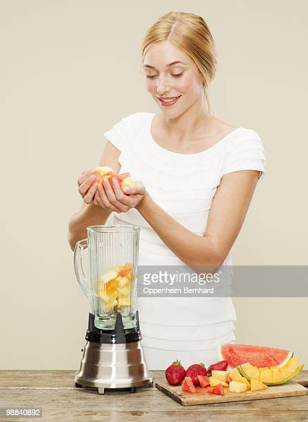 female placing ingredients into blender