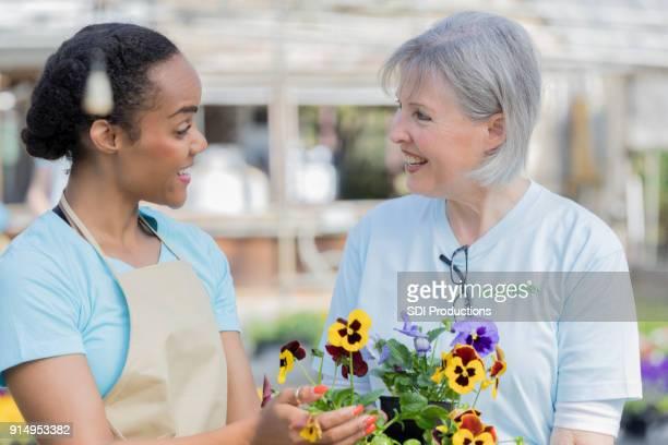 Female plant nursery employee assists senior woman