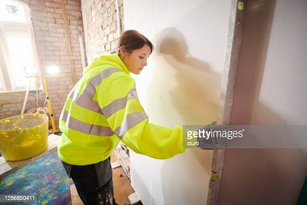 female plasterer applying board - sturti stock pictures, royalty-free photos & images