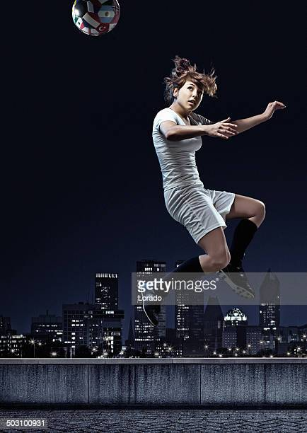 Female player heading the ball against night city background