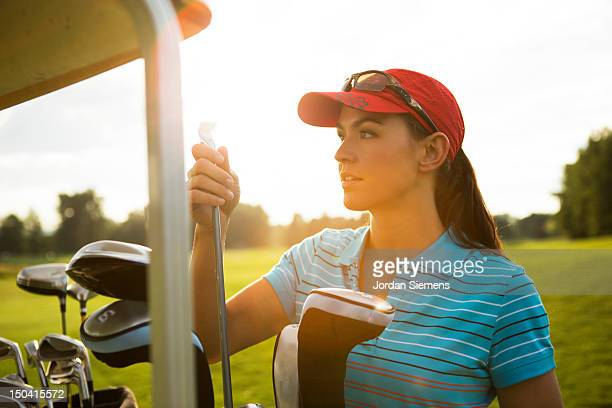 A female playing a round of golf.