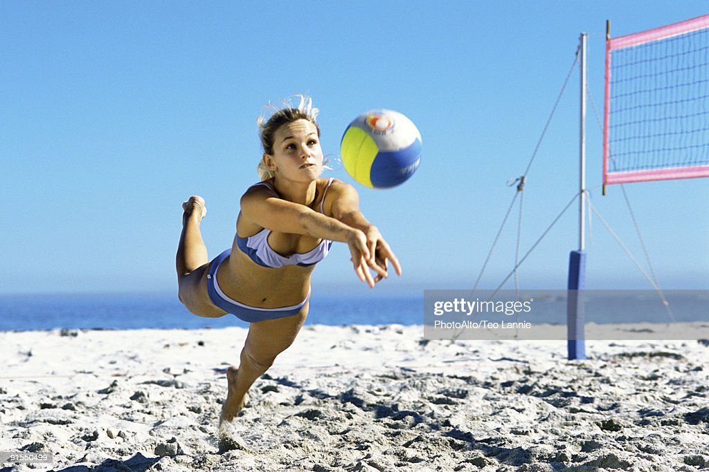 Female playing beach volleyball diving to catch ball : Stock Photo