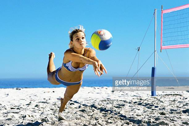 female playing beach volleyball diving to catch ball - beachvolleybal stockfoto's en -beelden