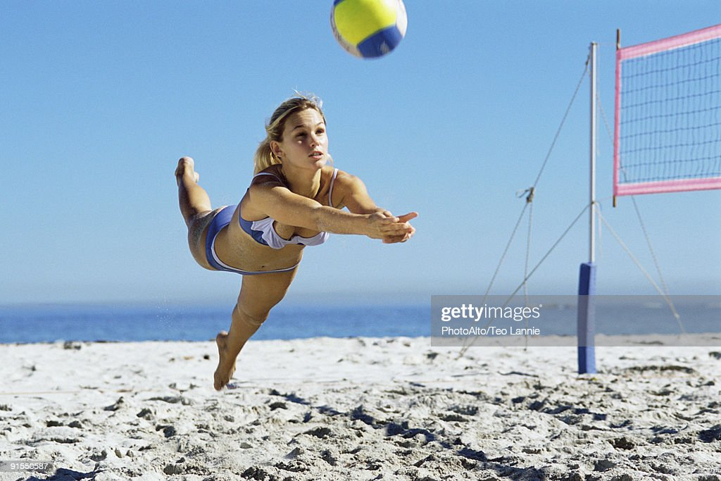 Female playing beach volleyball, diving to catch ball : Stock Photo