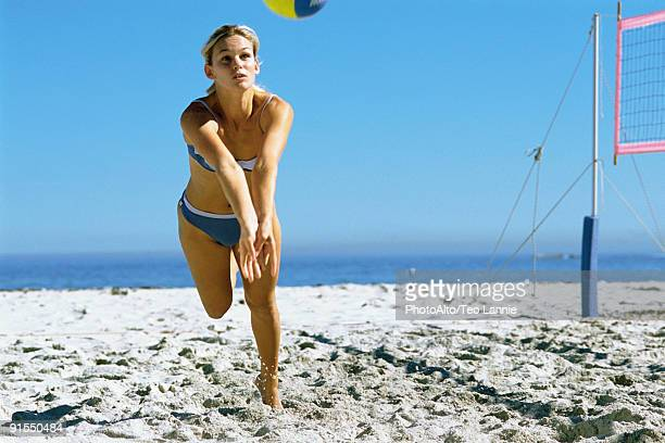 Female playing beach volleyball running to catch ball