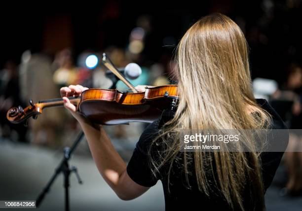 Female playing violin in front of audience
