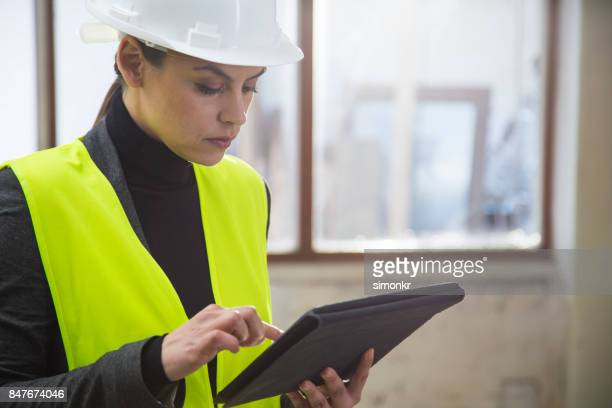 female plumber holding digital tablet - jacket stock pictures, royalty-free photos & images