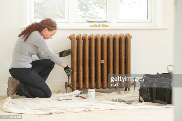 female plumber installing cast iron radiator - adjusting stock pictures, royalty-free photos & images