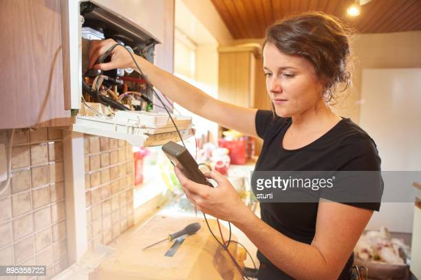 female plumber repairing a boiler - adjusting stock pictures, royalty-free photos & images